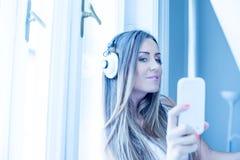听到在耳机的音乐的美丽的少妇 库存照片