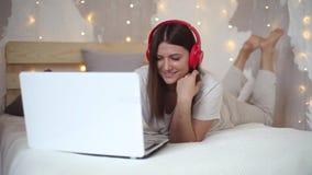 听到在耳机的音乐的美丽的性感的女孩使用充满说谎在床上的好心情的膝上型计算机 股票视频