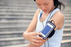 听到在耳机的音乐的赛跑者运动员从巧妙的电话MP3播放器 免版税库存照片