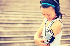 听到在耳机的音乐的赛跑者运动员从巧妙的电话MP3播放器 库存照片
