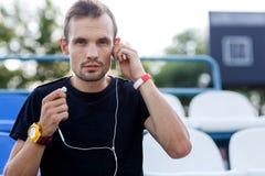 听到在耳机的音乐的运动的年轻男性在体育场内 库存照片
