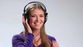 听到在耳机的音乐的逗人喜爱的微笑的女孩 股票视频