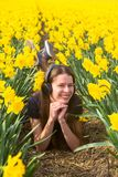 听到在耳机的音乐的青少年的女孩在花 免版税库存照片
