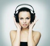 听到在耳机的音乐的年轻人和适合十几岁的女孩 库存图片