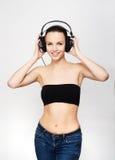 听到在耳机的音乐的年轻人和适合十几岁的女孩 免版税图库摄影