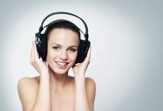 听到在耳机的音乐的年轻人和适合十几岁的女孩 免版税库存照片
