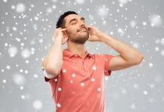 听到在雪背景的音乐的愉快的人 库存图片