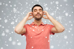 听到在雪背景的音乐的愉快的人 图库摄影