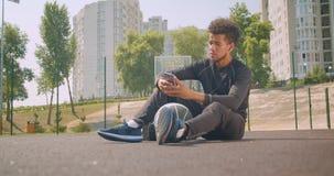 听到在震动的音乐的年轻坚强的非裔美国人的男性篮球运动员特写镜头画象在他的电话 股票录像