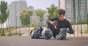 听到在震动的音乐的年轻英俊的非裔美国人的男性篮球运动员特写镜头画象在他的电话 股票视频