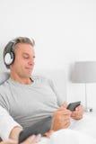 听到在他的智能手机的音乐的微笑的人 库存图片