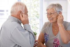听到在MP3播放器的音乐的年长夫妇 库存图片