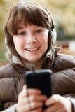 听到在Smartphone的音乐的男孩 免版税图库摄影