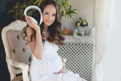 听到您喜爱的音乐的孕妇 图库摄影