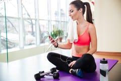 听到音乐和使用智能手机的愉快的女运动员在健身房 免版税图库摄影