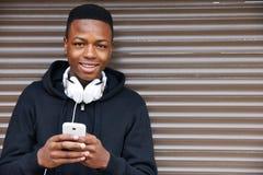 听到音乐和使用电话的十几岁的男孩在城市布局 免版税库存照片