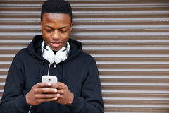 听到音乐和使用电话的十几岁的男孩在城市布局 库存照片