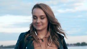听到音乐和跳舞沿河岸的逗人喜爱的年轻女人 影视素材