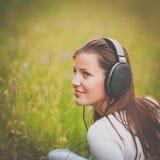 听到音乐的一个相当少妇的画象 库存照片