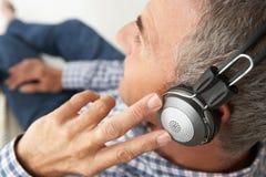 听到音乐的中间ag人通过耳机 免版税图库摄影