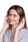 听到音乐的俏丽的妇女通过耳机 库存照片