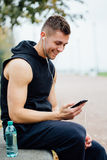 听到音乐的健身人佩带的运动服坐一条石长凳 在坚硬锻炼以后放松,谈话 图库摄影