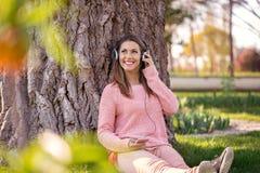 听到音乐的华美的少妇在公园 免版税库存照片