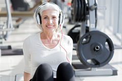 听到音乐的喜悦的资深妇女在锻炼以后 库存图片