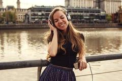 听到音乐的女孩享用与她的眼睛关闭了 免版税库存照片