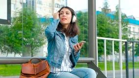 听到音乐的女孩在现代公交车站 股票视频