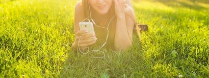 听到音乐的女孩放出与耳机在草甸的夏天 免版税库存照片