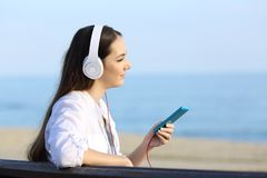 听到音乐的女孩放松在海滩 免版税库存照片