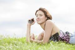 听到音乐的妇女侧视图通过MP3播放器使用耳机,当说谎在草反对天空时 免版税库存图片