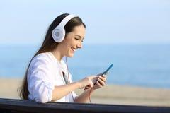 听到音乐的妇女坐在海滩的一条长凳 库存图片