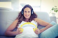 听到音乐的孕妇在客厅 库存照片