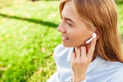 听到音乐的少女通过无线耳机户外 免版税库存图片