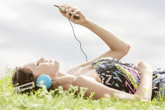 听到音乐的少妇侧视图通过MP3播放器,当说谎在草反对天空时 图库摄影