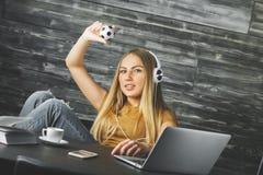 听到音乐的少妇在工作场所 免版税库存照片