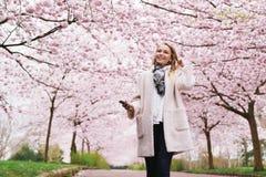 听到音乐的少妇在春天公园 免版税库存图片