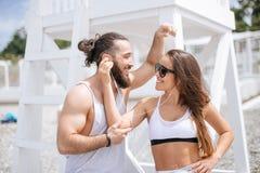 听到音乐的年轻夫妇使用一在海滩的耳机 免版税图库摄影