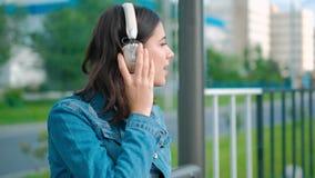 听到音乐的年轻女人坐长凳 股票录像