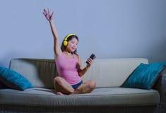 听到音乐的年轻美丽和甜亚裔韩国妇女放松了和愉快在家坐拿着手机的沙发长沙发 免版税库存图片