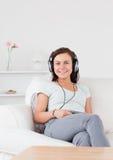 听到音乐的微笑的妇女 免版税库存图片