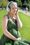 听到音乐的怀孕的白肤金发的女孩 库存图片