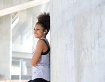 听到音乐的愉快的可爱的年轻黑人妇女 免版税库存照片