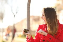 听到音乐的愉快的女孩唱歌和跳舞在公园 免版税库存照片