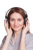 听到音乐的愉快的少妇通过耳机 库存照片