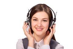 听到音乐的愉快的少妇通过耳机 免版税库存照片
