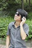 听到音乐的愉快的年轻人 图库摄影