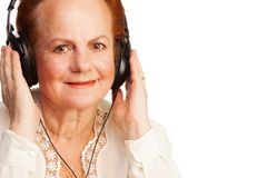 听到音乐的正退休的妇女 库存图片